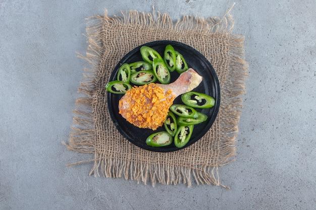 Baqueta marinada e pimenta fatiada em prato sobre guardanapo de estopa, sobre superfície de mármore.