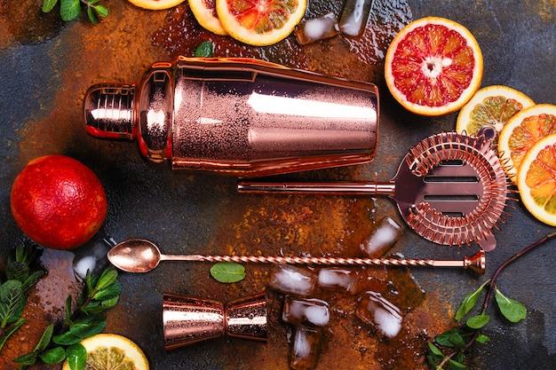 Bar acessórios, ferramentas de bebida e ingredientes de cocktails na mesa de pedra enferrujada.