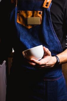 Bar concurso com avental jeans detém um copo