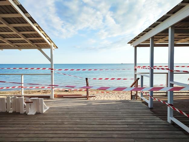 Bar da praia fechado com fita de advertência devido a reconstrução ou restrições para pandemia de coronavírus
