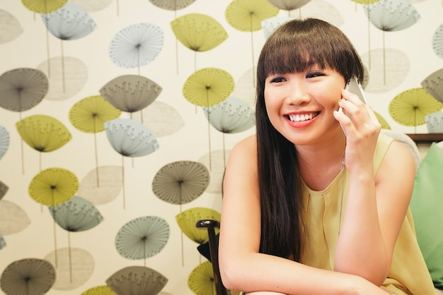Bar inteligente casual jovem asiática falando no smartphone. adulto feminino feliz falando no celular.