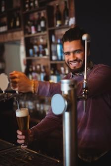 Bar tender enchendo cerveja de bar pump