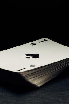 Baralho de cartas amarelado velho no fundo preto. o ás de espadas está no topo.