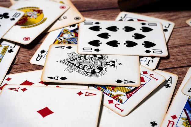 Baralho de cartas de pôquer espalhado sobre uma mesa de madeira. foco seletivo.