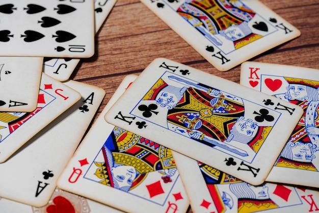 Baralho de cartas de pôquer espalhado sobre uma mesa de madeira.