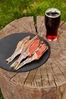 Barata seca ao sol com ovas e copo de cerveja preta no toco de madeira
