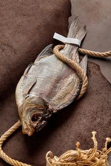 Barata seca salgada com etiqueta de papel na cauda e corda grossa no fundo de couro