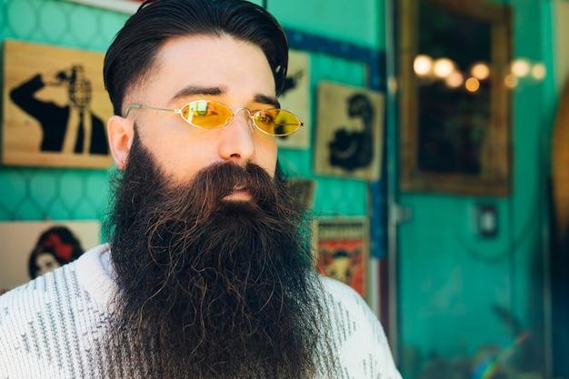 Barba considerável jovem com óculos amarelos, olhando para longe