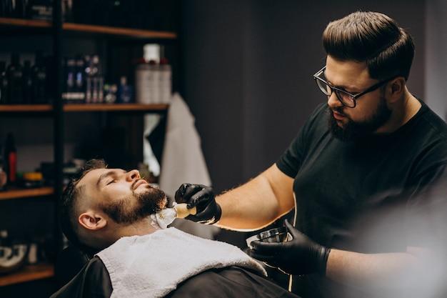 Barba de corte de homem bonito em um salão de barbeiro