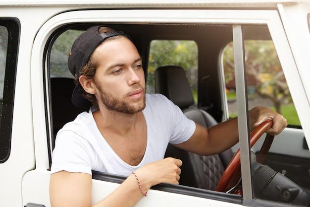 Barba por fazer jovem bonito vestindo camiseta casual e boné de beisebol para trás, olhando pela janela aberta de seu veículo com tração nas quatro rodas, indo em viagem de safari