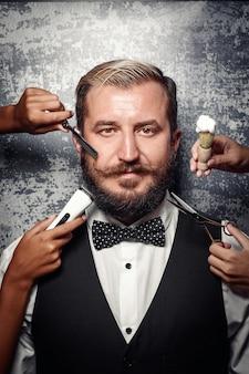 Barbeador elétrico, lâmina, escova de espuma e tesoura perto do rosto do homem