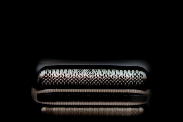 Barbeador elétrico masculino moderno em fundo escuro