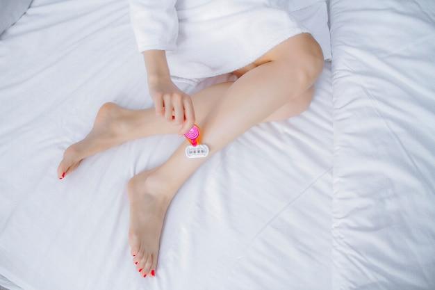 Barbeando os pés com uma lâmina em um fundo branco. a menina raspa as pernas. depilação das pernas com uma navalha.