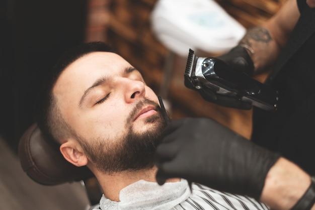 Barbear uma barba em uma barbearia com uma navalha perigosa. barber shop beard care. secar, cortar, cortar uma barba. foco seletivo.