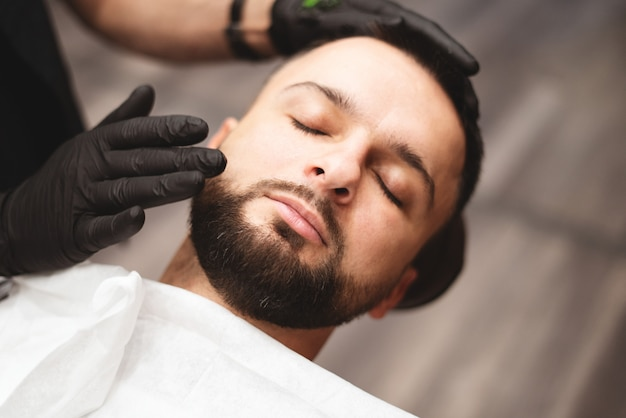 Barbear uma barba em uma barbearia com uma navalha perigosa.