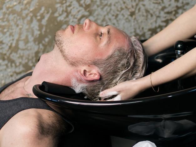 Barbearia. barbeiro mulher lavando a cabeça do homem, vista lateral