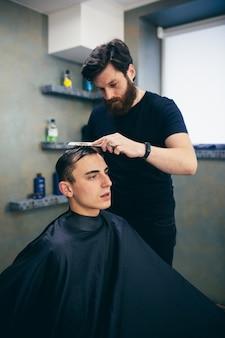Barbearia. homem corta o cabelo de outro homem. faz um penteado