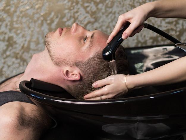 Barbearia. mãos de mulher lavando a cabeça do homem, vista lateral
