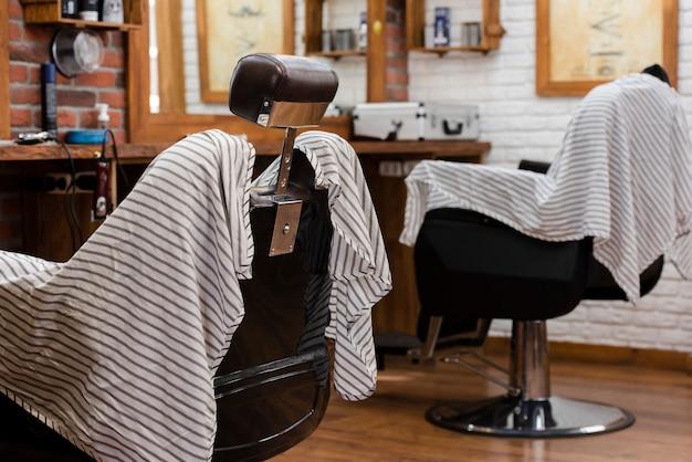 Barbearia profissional com cadeiras vazias