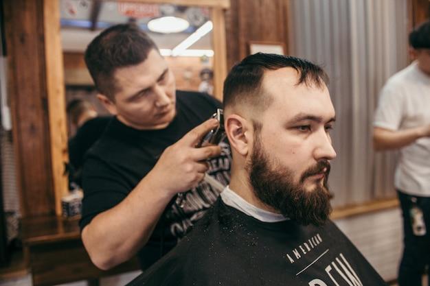 Barbearia, um homem com um cabeleireiro de corte de barba, corte de cabelo profissional