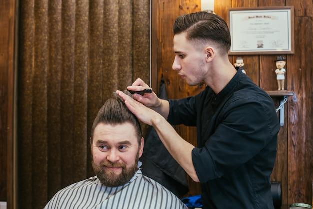 Barbearia, um homem com um cabeleireiro de corte de barba