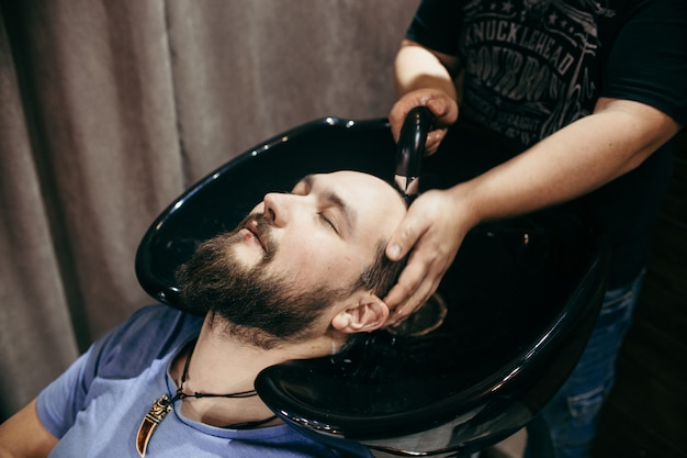 Barbearia, um homem com uma barba cortada. corte de cabelo profissional, penteado retrô e estilo. cabelos e cuidados bonitos, salão de cabeleireiro para homens. atendimento ao cliente.