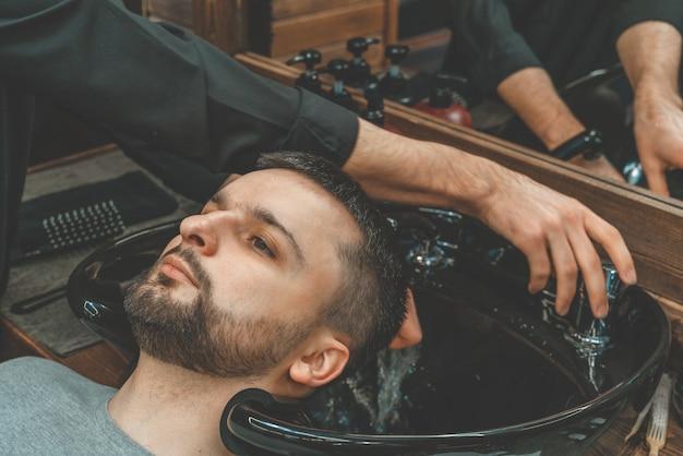 Barbearia, um homem é lavado o cabelo. barber lava seu cliente. lave os cabelos e as barbas após o corte. cuidado pessoal