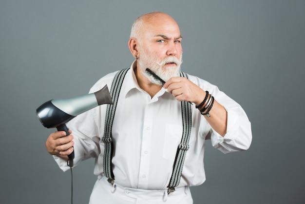 Barbearia vintage, barbear-se. barbeiro cabeleireiro maduro com secador de cabelo e penteado para secar a barba e bigode.