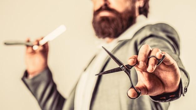 Barbearia vintage, fazendo a barba. homem barbudo do retrato. barbearia vintage. cara brutal, tesoura, navalha. cliente barbudo visitando a barbearia.