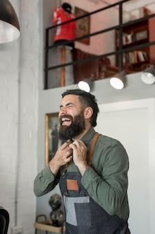 Barbeiro adulto em uniforme rindo no salão de cabeleireiro