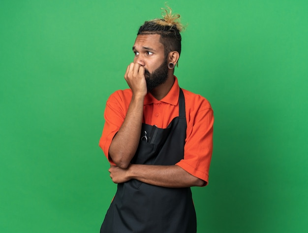 Barbeiro afro-americano jovem e ansioso vestindo uniforme, colocando a mão na boca, olhando para o lado isolado na parede verde com espaço de cópia