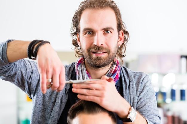 Barbeiro aparando cabelo de homem em loja de corte de cabelo