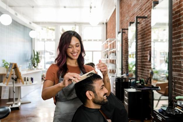 Barbeiro aparando o cabelo de um cliente em uma barbearia