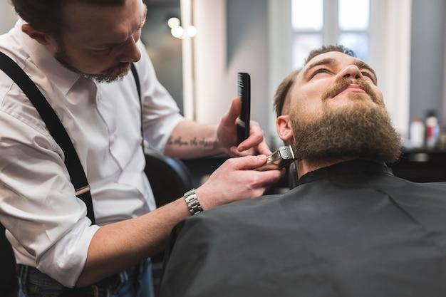 Barbeiro aparar barba do cliente