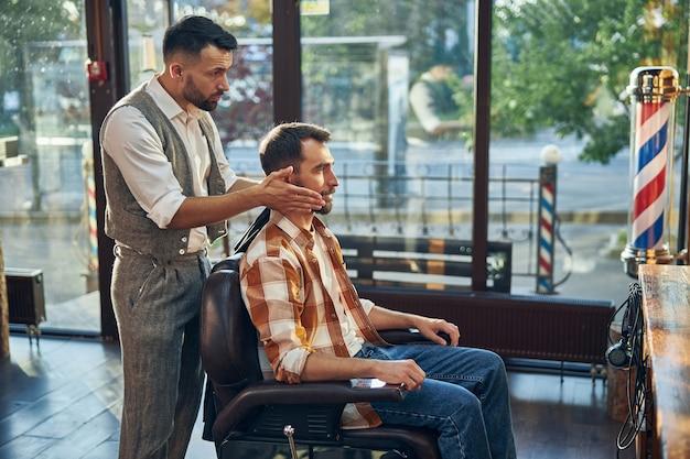 Barbeiro atento atrás de seu cliente e segurando sua cabeça enquanto se olha no espelho
