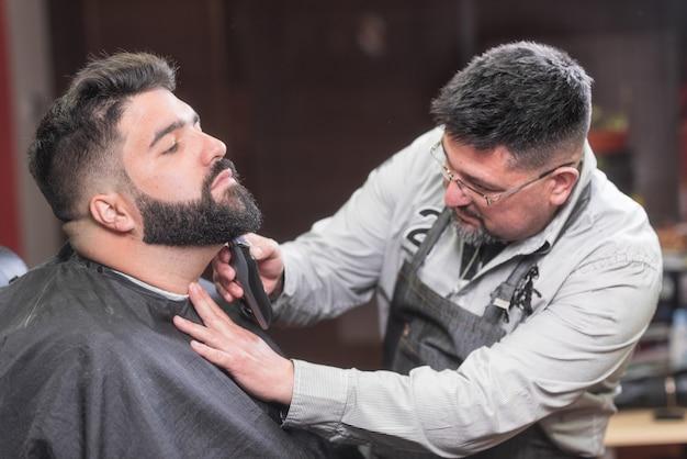 Barbeiro barbeando a barba de um homem barbudo bonito com um barbeador elétrico na barbearia.
