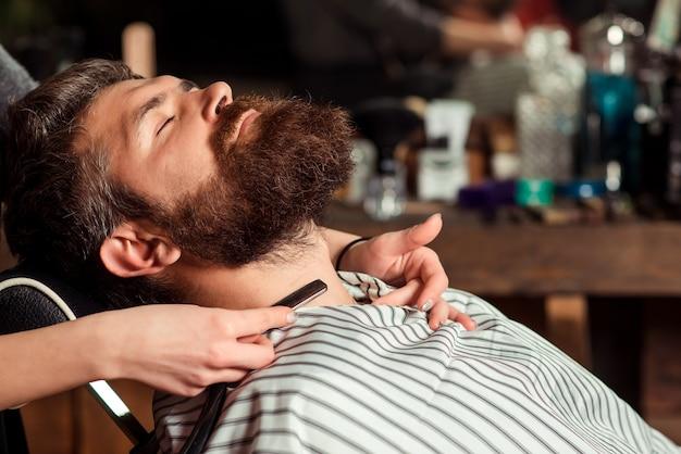 Barbeiro barbeando um homem barbudo