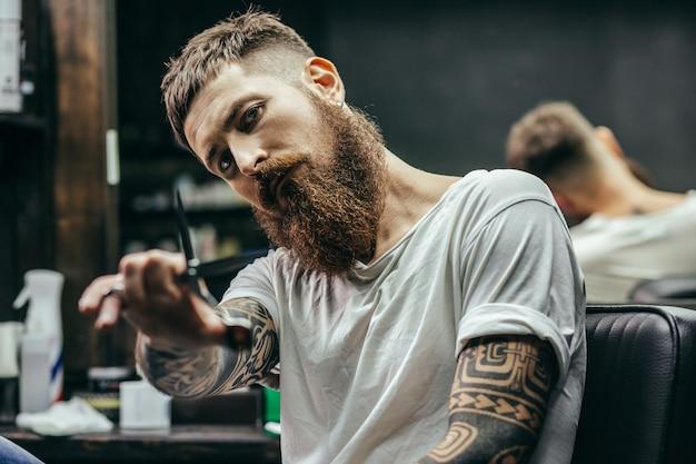 Barbeiro barbudo calmo e pensativo com tatuagens nos braços, sentado e olhando enquanto abre uma tesoura