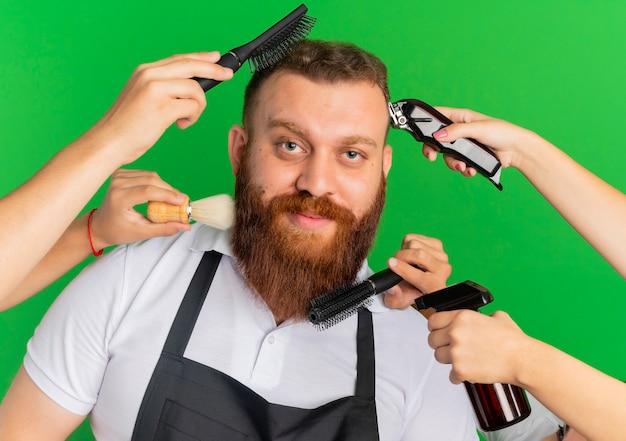 Barbeiro barbudo de avental sorrindo, tendo seu corte de cabelo e sua barba modelados por outras mãos sobre a parede verde