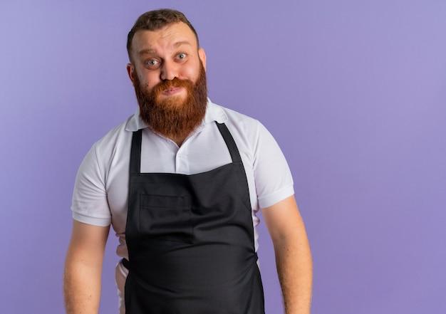Barbeiro barbudo profissional alegre de avental soprando as bochechas em pé sobre a parede roxa