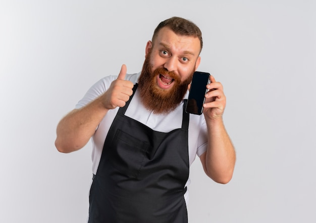 Barbeiro barbudo profissional com avental feliz e animado falando no celular, mostrando os polegares em pé sobre uma parede branca