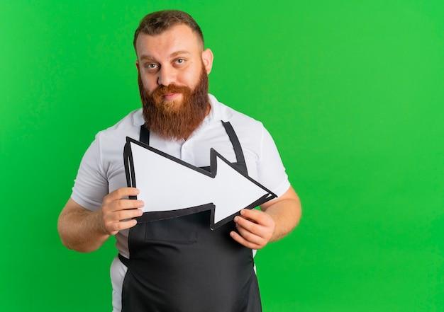 Barbeiro barbudo profissional com avental segurando uma grande seta com rosto sério em pé sobre a parede verde