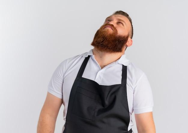 Barbeiro barbudo profissional preocupado com avental olhando para cima em pé sobre uma parede branca