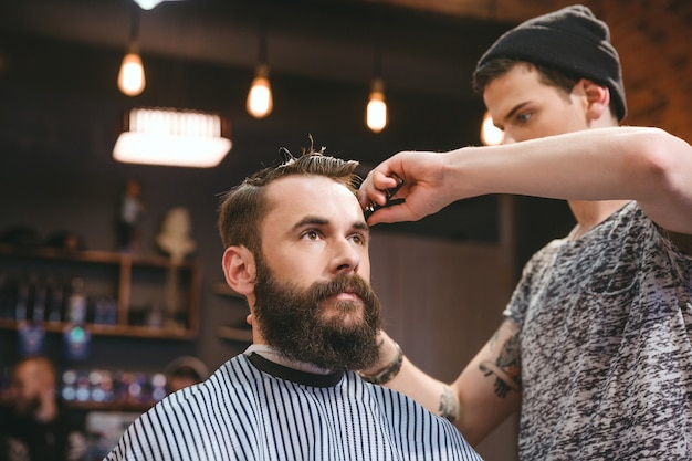 Barbeiro bonito e habilidoso cortando o cabelo de um jovem atraente com barba na barbearia