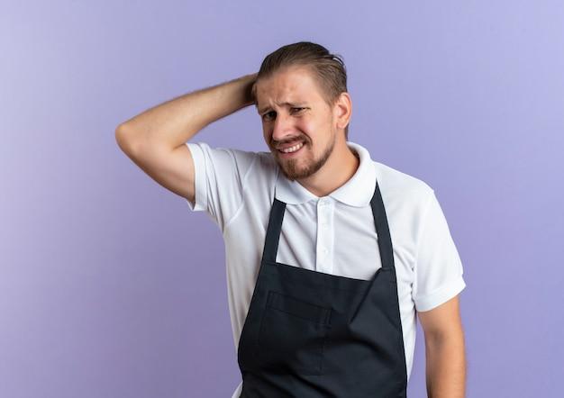 Barbeiro bonito jovem e desagradável vestindo uniforme, colocando a mão atrás da cabeça, isolado no fundo roxo