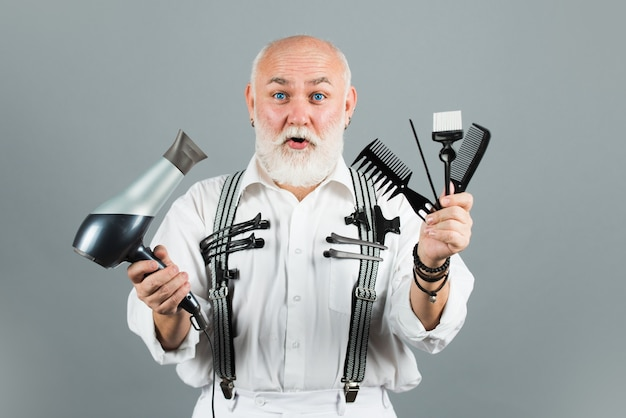 Barbeiro cabeleireiro maduro na barbearia. velho barbeiro surpreso e animado com ferramentas de equipamento de barbeiro.