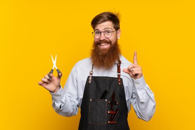 Barbeiro com barba longa em um avental sobre fundo amarelo isolado, apontando para cima uma ótima idéia