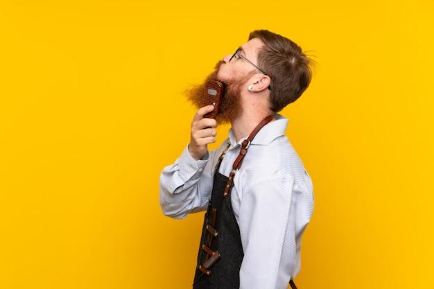 Barbeiro com barba longa em um avental sobre fundo amarelo isolado