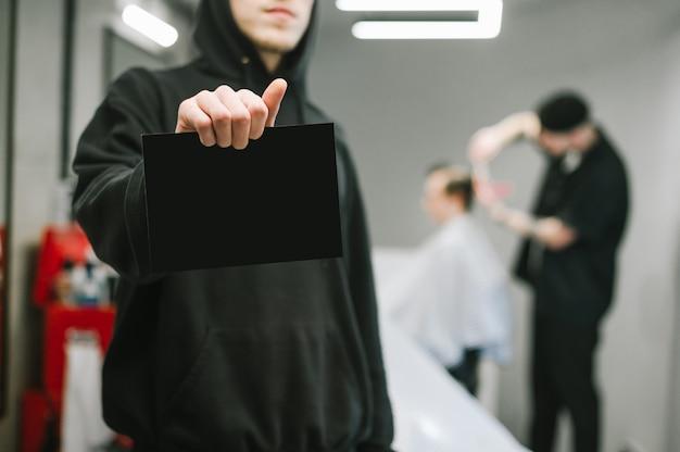 Barbeiro com capuz escuro detém um cartão para copyspace em um cabeleireiro masculino e clientes de recorte de barbeiro
