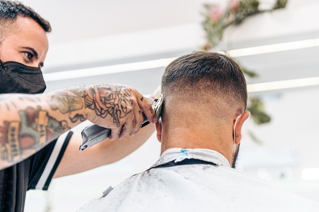 Barbeiro com máscara cortando cabelo de cliente usando máquina de barbear elétrica em salão de beleza